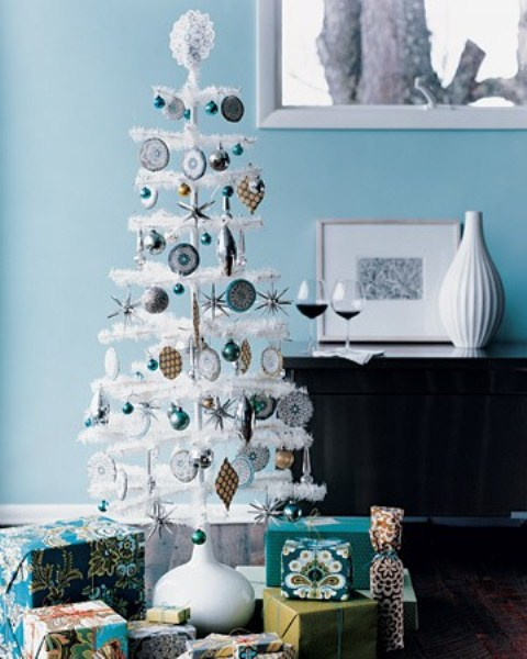 a white tabletop Christmas tree with silver and blue ornaments, with a lace topper and some mini ornaments