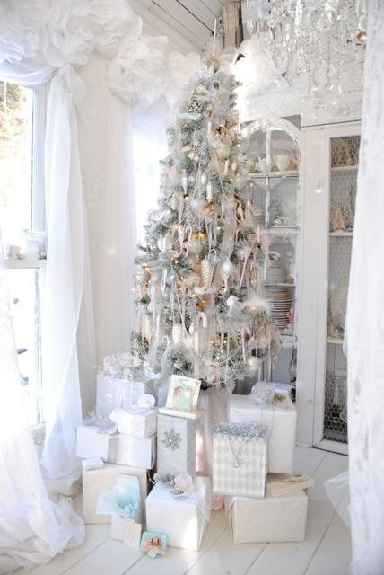 a snowy Christmas tree with lights and silver and white ornaments plus ribbons looks very frozen, chic and elegant