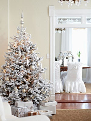 a snowy Christmas tree with lights and white and sivler ornaments to match its frozen beauty