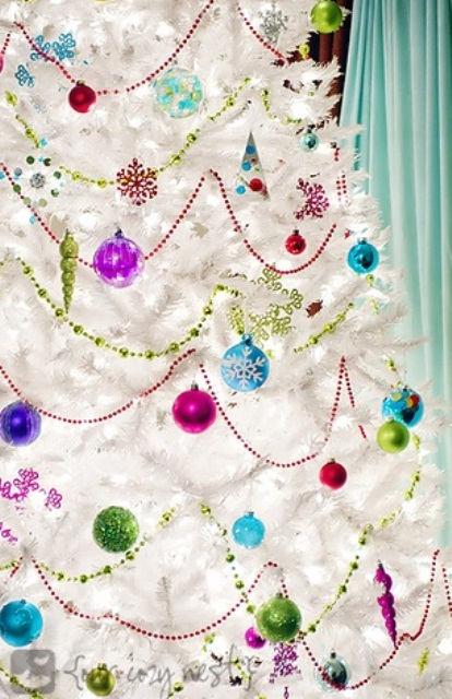 a white Christmas tree with super bright and colorful ornaments and garlands to contrast it for a bold look