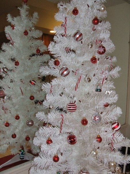 a white Christmas tree with white and red ornaments that contrast it and create a bold and bright festive ambience