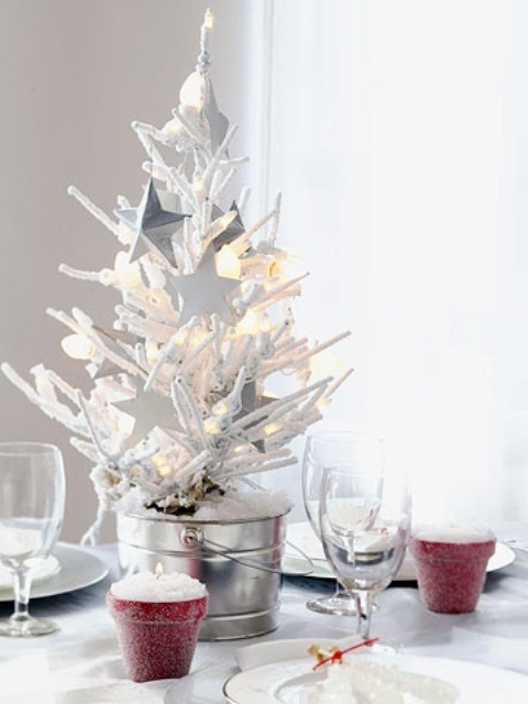 a mini snowy Christmas tree in a galvanized bucket, with lights and white star ornaments for a centerpiece