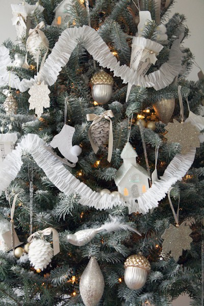 a muted Christmas tree with lights, silver, white and gold ornaments, paper garlands, shiny snowflakes and other stuff