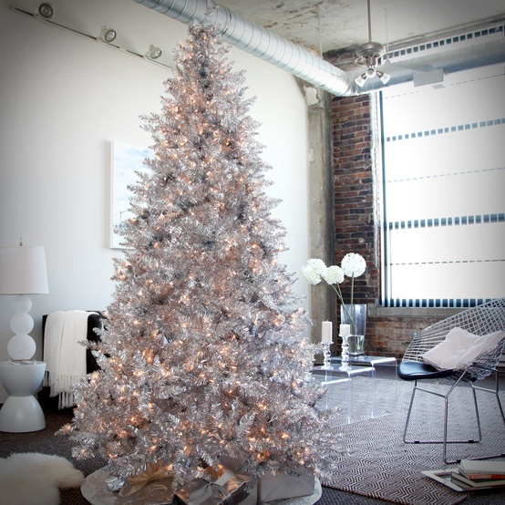 a shiny silver Christmas tree with lights is a glam and bright idea, no additional decor required