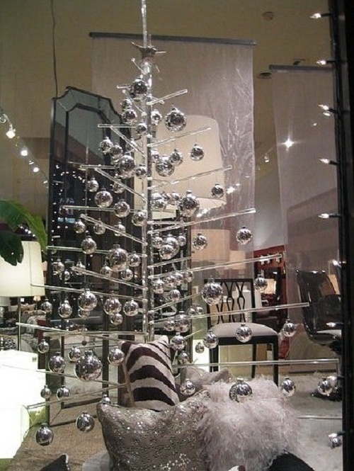a sheer acrylic Christmas tree with shiny silver ornaments and silver and white pillows under the tree