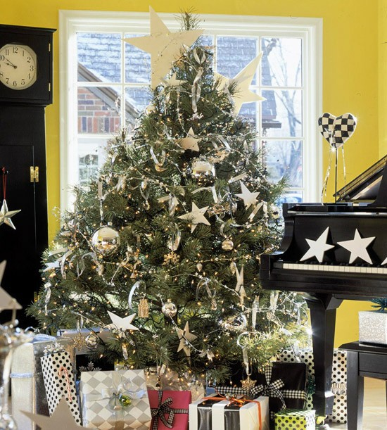 a traditional Christmas tree with large silver ball ornaments and stars, snowflakes and lights plus garlands