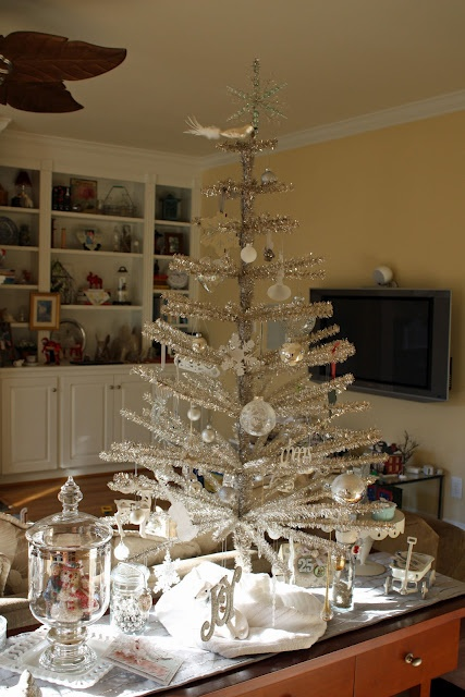 a shiny silver Christmas tree with white and silver ball and snowflake ornaments can be a nice tabletop decoration