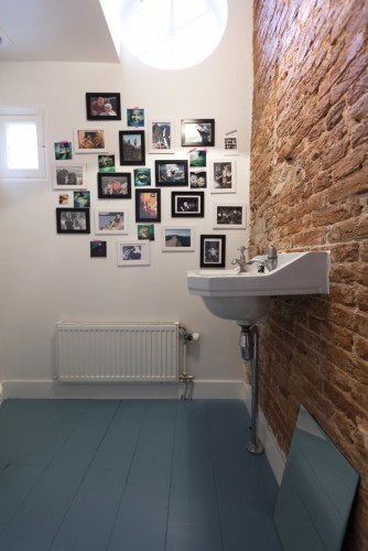 Combination of a modern gallery wall with a brick wall is a stylish solution for creative interiors.