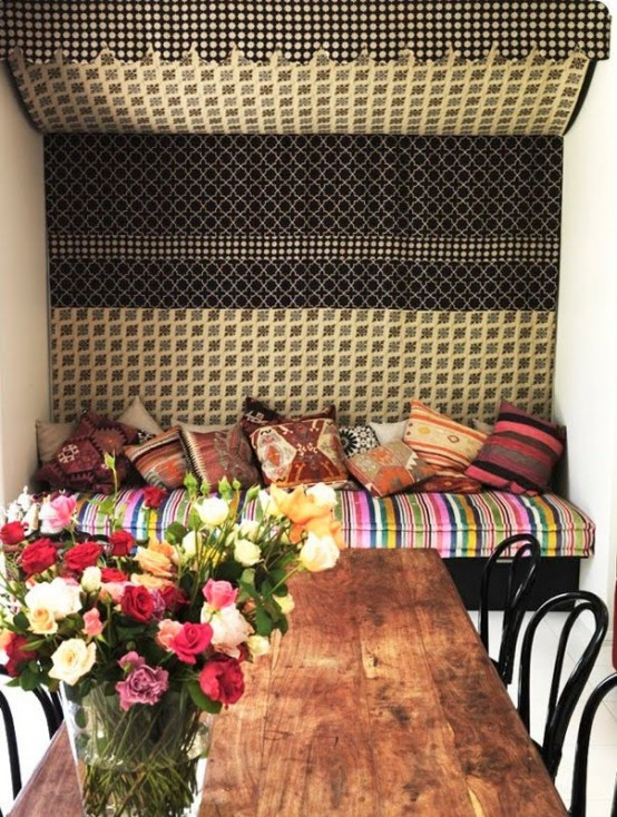 a stylish Moroccan dining room with a wooden table and black chairs, a bright upholstered bench and a bold tapestry over the bench