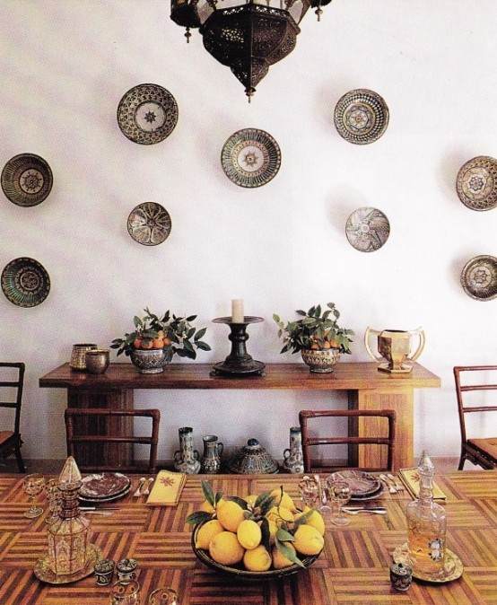 a Moroccan dining room with light stained wooden furniture, decorative plates on the wall, Moroccan lanterns and lamps on the table