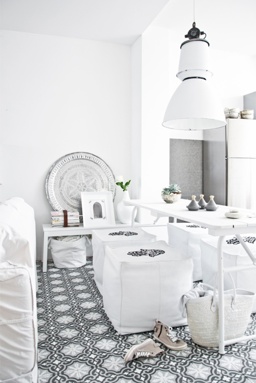 a neutral Moroccan dining room with a printed tile floor, white furniture and printed poufs, a chic plate for decor and potted plants