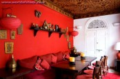 a bold red Moroccan dining room with a hot red accent wall, a shelf and red paper lamps, a dark table and an upholstered bench, a patterned ceiling and red chairs