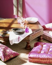 a pink Moroccan dining space wiht a low hexagon table, pink and fuchsia printed pillows looks boho chic and welcoming