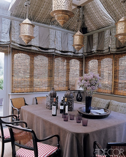 a neutral Moroccan dining space with a table covered with a mauve tablecloth, printed chairs, Moroccan lanterns on the table and over the space and neutral printed textiles