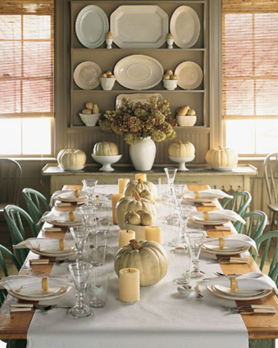 a neutral-white fall table setting with a white table runner, neutral pillar candles and neutral real pumpkins is very cozy and chic
