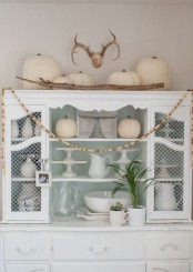 a white vintage sideboard with white pumpkins, branches, wooden beads and elegant white tableware