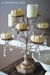 a refined metal stand with crystals, white pillar candles and pumpkins is a very cool idea to go for