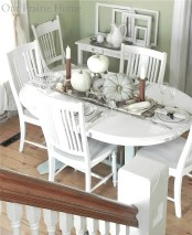 a white fall tablescape with white furniture, white linens, pumpkins, hay, pinecones and candles