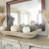 a dough bowl with moss balls and white pumpkins is a great all-natural decoration for the fall
