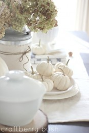 place white pumpkins into white plates to make your tablescape feel refined, rustic and fall-like