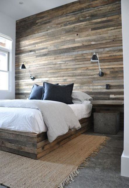 a statement headboard wall fully clad with weathered wood and a matching wooden slab bed for a cozy rustic look