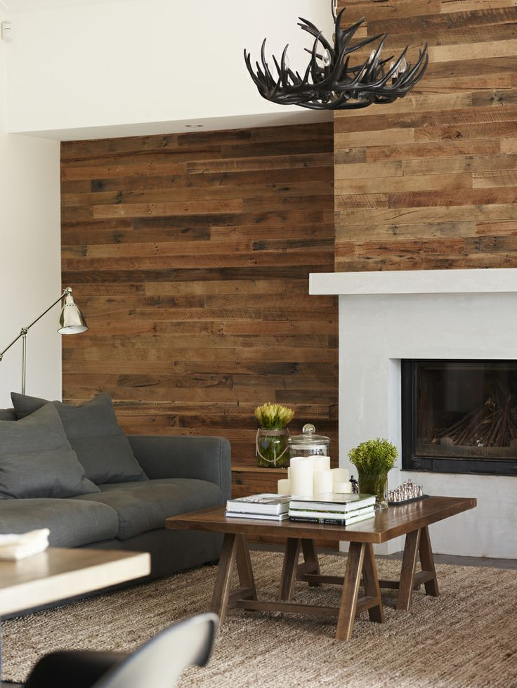 light stained weathered wood walls, a stained coffee table and an anlter chandelier make the space cozy and add a rustic feel