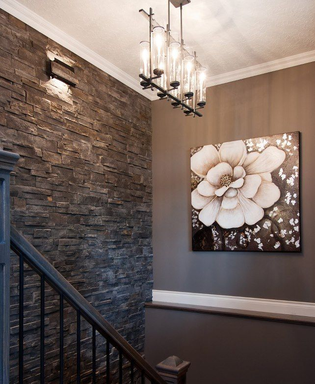 a dark textural wall of faux stone adds interest to the space and makes it chic and catchy