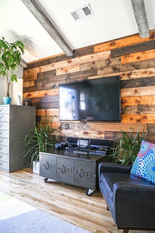 a weathered and stained wood accent wall softens the industrial-inspired living room with vintage touches