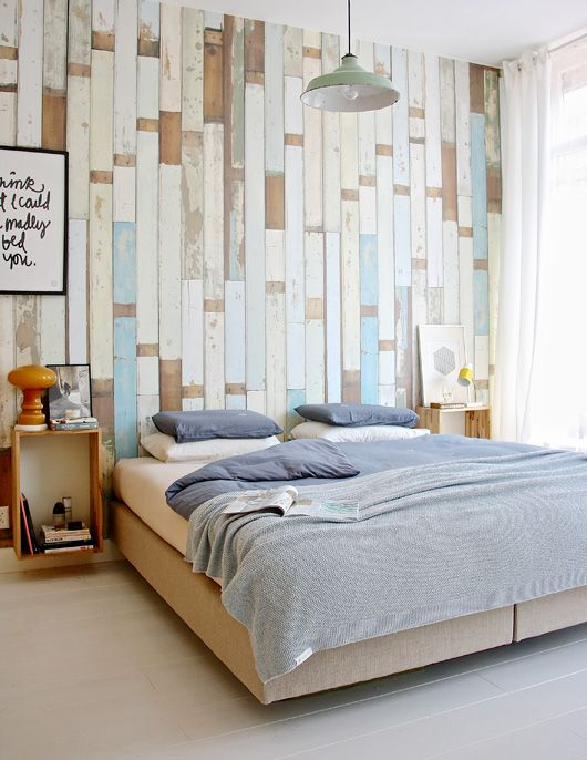 an accent wall done with various shabby wooden planks in white, beige and blue adds a nonchalant touch to the bedroom