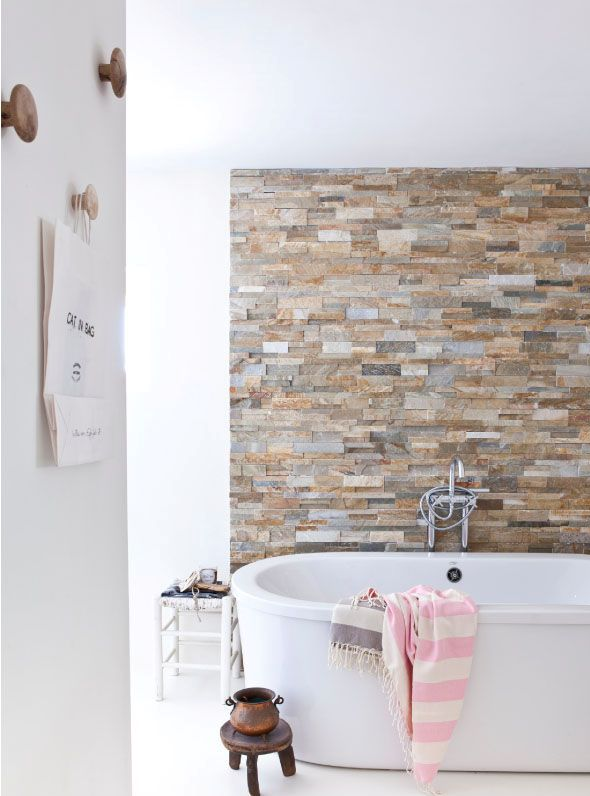 an earthy colored faux stone accent wall is a gorgeoys way to spruce up a neutral contemporary bathroom