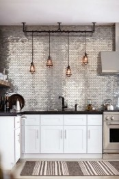 a shiny silver tile accent wall and backsplash makes the monochromatic kitchen bolder and brighter