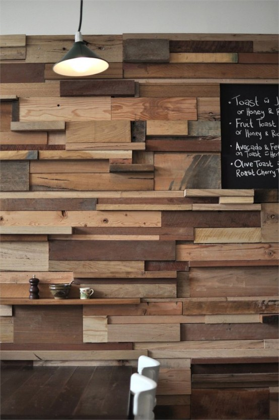 a unique accent wall done with lots of wooden slabs and planks in various colors adds a rustic and industrial touch