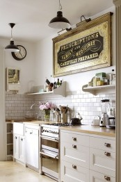 a beautiful neutral kitchen with paned cabinets and knobs, a white subway tile backsplash, open shelves, a vintage artwork and vintage pendant lamps