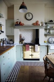 a vintage kitchen with blue cabinets, butcherblock and stone countertops, a vintage cooker, a clock and a pendant lamp plus a black and white checked floor
