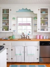 a vintage kitchen in white, with a beadboard backsplash, butcherblock countertops, touches of blue, mint green and pink is lovely