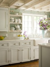 a neutral vintage kitchen with pane cabinets, a white stone countertops, a white subway tile backsplash, mint green backsplash and open shelves is cool