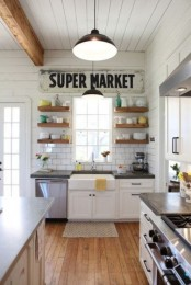a pretty white vintage kitchen with white cabinets, black countertops, open shelves, pendant lamps and a wooden kitchen island