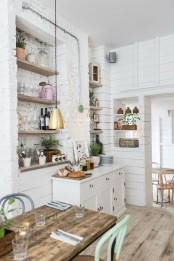a vintage Scandinavian kitchen with white cabinets, built-in shelves, a rough wooden table, pastel chairs and pendant lamps