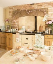 a beautiful vintage kitchen with warm-stained cabinets, black coutnertops, a vintage cooker, touches of pink and floral textiles
