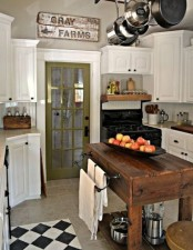 a stylish vintage kitchen with white cabinets, a dark stained kitchen island and cart in one, a green door and a vintage shabby chic sign
