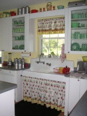 a vintage kitchen with white cabinets, glass and usual ones, yellow walls, touches of green and red and floral textiles