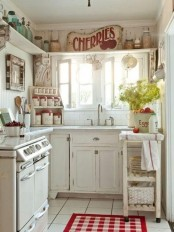 a pretty vintage kitchen in white, with chic cabinets, a long open shelf for storage, a tiny cart as a kitchen island and touches of red and mint green