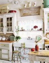 a vintage kitchen with shabby chic white and green cabinets, a shabby chic display shelf, a crystal chandelier and some plaid and floral textiles