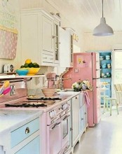 a candy-colored vintage kitchen with blue and pink cabinets, a pink fridge, a pink cooker, printed textiles and surfaces