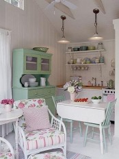 a neutral vintage kitchen with built-in cabinets, a green buffet, a folding table and blue chairs, colored tableware and chairs with floral upholstery