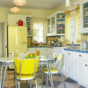 a colorful vintage kitchen in bright yellow and blues, with yellow walls and a backsplash, a blue countertop, a yellow fridge, yellow chairs and blue shelves is fun