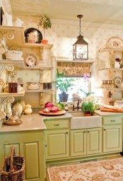 a vintage kitchen with green cabinets, open shelves, floral print wallpaper, vintage decor, pendant candle lanterns and printed rugs