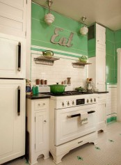 a contrasting vintage kitchen with green walls and white cabinets, a penny tile floor, a white tile backsplash and black touches