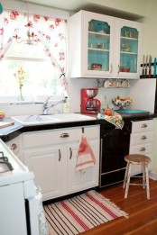 a vintage kitchen with white walls and cabinets, black countertops, floral textiles and touches of bright blue