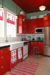 a vintage kitchen with green walls, red cabinets, usual and glass ones, a tiled countertop and some floral and fruit prints